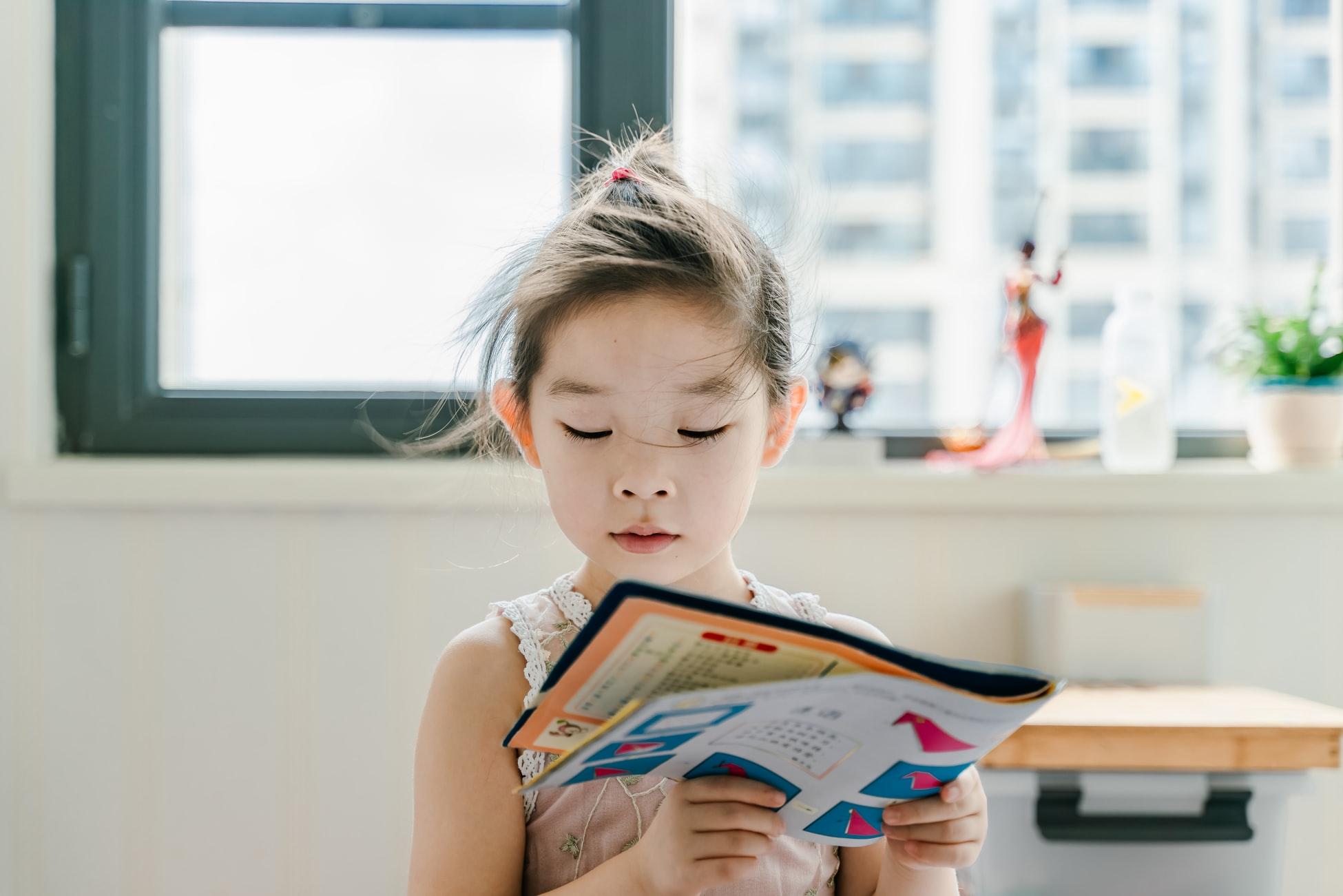kid reading oragami book